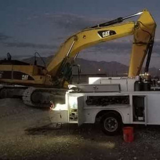 Welding heavy equipment (track hoe) at night